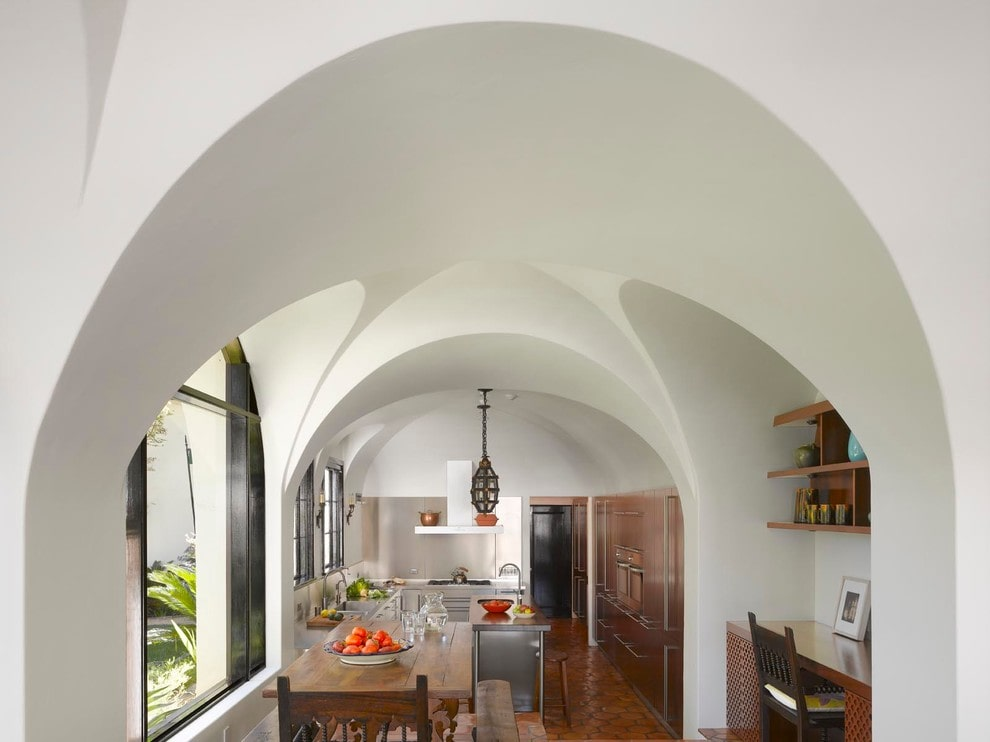 Beautiful groin vault ceiling dominates this eat-in kitchen showcasing full height cabinets and a wood top island lit by caged pendant lights. It has aluminum framed windows and terracotta flooring arranged in a herringbone pattern.