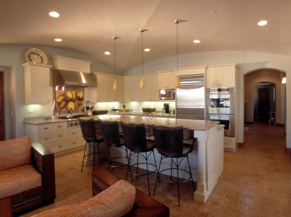 An open concept kitchen with inset appliances and white cabinetry matching with the beadboard island that's topped with granite countertops. It is lined with frosted glass pendants and metal bar chairs over warm limestone flooring.