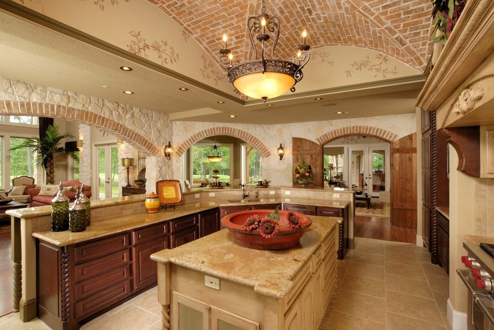 Classic kitchen with open archways and a groin vault ceiling designed with bricks and floral mural. It is filled with dark wood cabinets and a two-tier kitchen bar along with a light wood island lit by an ornate pendant light.