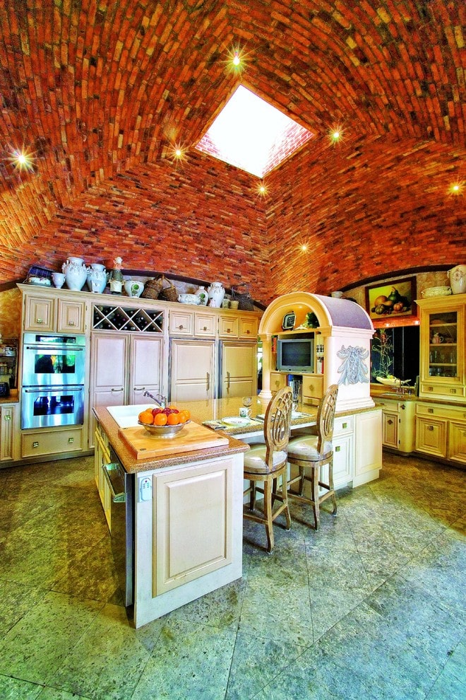 Traditional kitchen features light wood cabinetry and an L-shaped island topped with an arched shelving that houses the TV. It has concrete tiled flooring and a marvelous groin vault ceiling fitted with recessed lights and a square skylight in the middle.