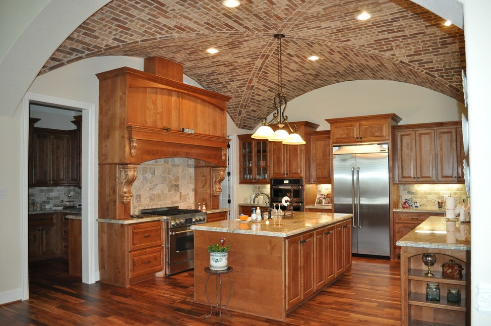 A view of the cozy kitchen through the open archway offering wooden cabinetry and a matching island that blends in with the hardwood flooring. It includes stainless steel appliances and a classic dome pendant that hung from the groin vault ceiling clad in bricks.