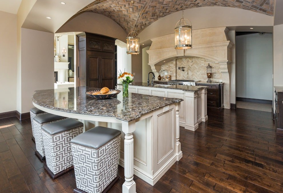 Stylish patterned stools complement the white breakfast island with a curved granite countertop over wide plank flooring. It is accompanied by dark wood cabinets and an arched cooking alcove accented with a herringbone backsplash that matches the groin vault ceiling.