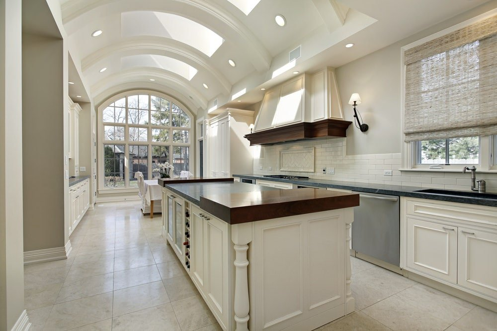This is a bright galley kitchen with a bright and white high ceiling that is arched and filled with skylights and recessed lights. This brightness is carried over onto the white shaker cabinets and drawers of the large kitchen island and the cabinetry lining the wall.