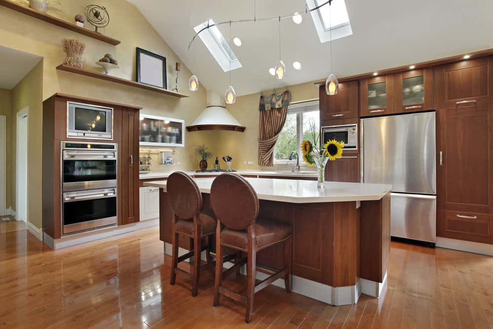 This is a charming kitchen with white white shed ceiling further brightened by the sky lights and the recessed lights. It complements the beige walls adorned with wooden shelves, and large wooden structures housing the appliances. These wooden structures pair well with the hardwood flooring.