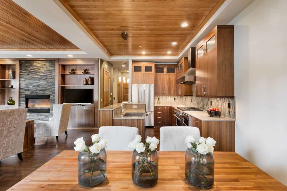 This charming and compact kitchen has a wooden tray ceiling with a shiplap finish that has recessed lights and hangs pendant lights over the kitchen island. The wooden tone of this ceiling matches with the L-shaped cabinetry of the walls and the hardwood flooring.