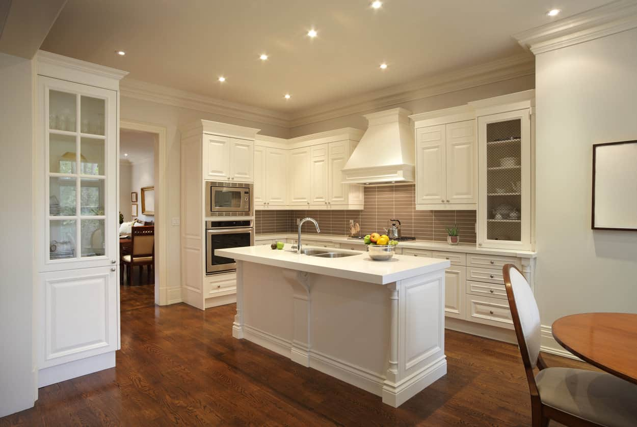 The bright narrow kitchen island of this elegant kitchen stands out against the dark hardwood flooring. This flooring also contrasts the bright white shaker cabinets and drawers of the wooden structure dominating the walls that is counterbalanced by a gray backsplash.
