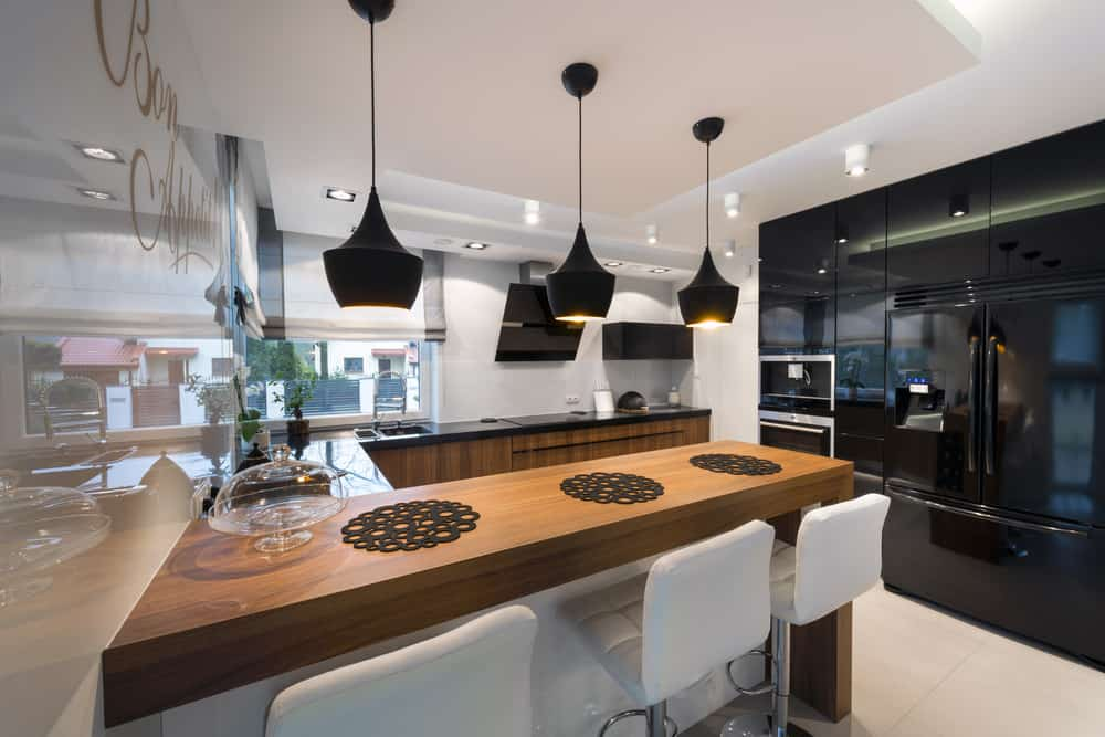 The black appliances of this modern kitchen gives it a special aesthetic of sophistication and luxury. This is augmented by the black pendant lights from the white ceiling hanging over the wooden breakfast bar contrasted by the white modern stools.