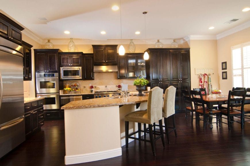 The rich dark wood flooring of this elegant dine-in kitchen blends perfectly with the dark wooden dining set as well as the shaker cabinets and drawers of the kitchen structures on the walls. They complement the stainless steel appliances making them pop out.