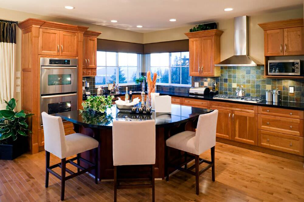 The double wall oven of this charming kitchen is housed in a tall wooden structure attached to the L-shaped cabinetry that follows the lay of the walls. It has a black countertop that matches with the kitchen island contrasted by the cushioned stools of the breakfast bar.