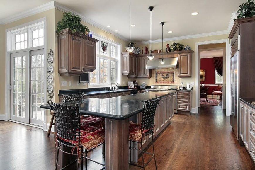 The extensive dark wood of this kitchen extends from the hardwood flooring to the wooden shaker cabinets of the beige walls and the large wooden structure housing the stainless steel fridge. It can also be seen on the large kitchen island paired with wrought iron stools to match the black countertop.