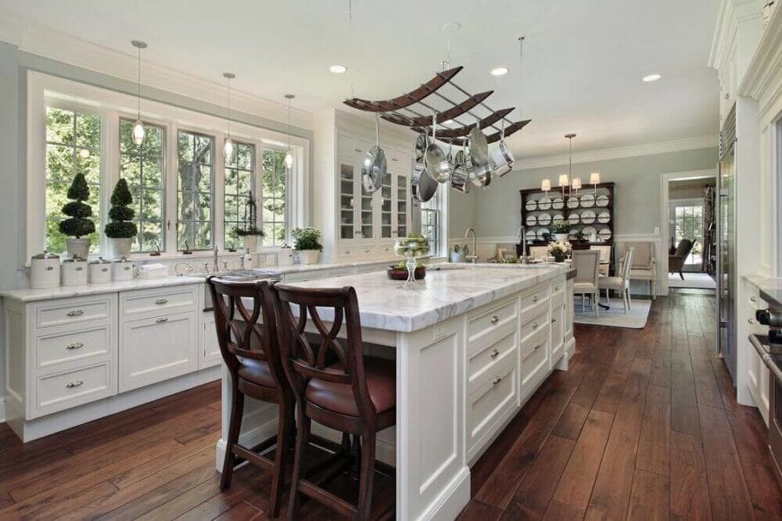 The large white kitchen island is topped with a curved hanging pot rack from the white ceiling brightened by recessed lights. This rack matches well with the other dark wooden elements of the gorgeous kitchen like the wooden chairs and the hardwood flooring.