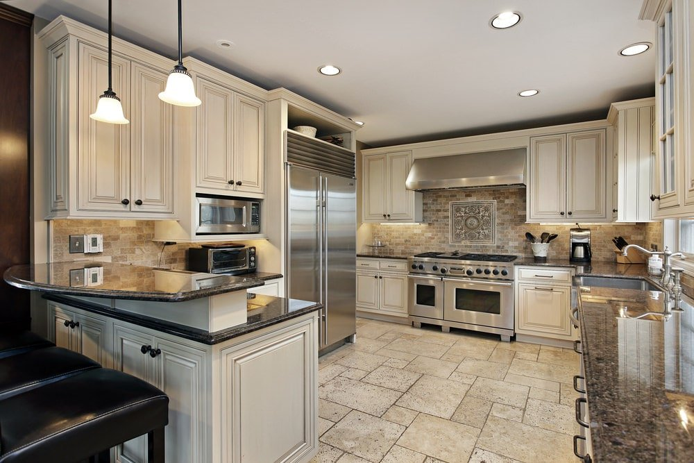 This charming spacious kitchen has an L-shaped peninsula with white white shaker cabinets paired with black countertops and a second tier to serve as a breakfast bar for the black cushioned stools. This is topped with a couple of small pendant lights hanging from the white ceiling.