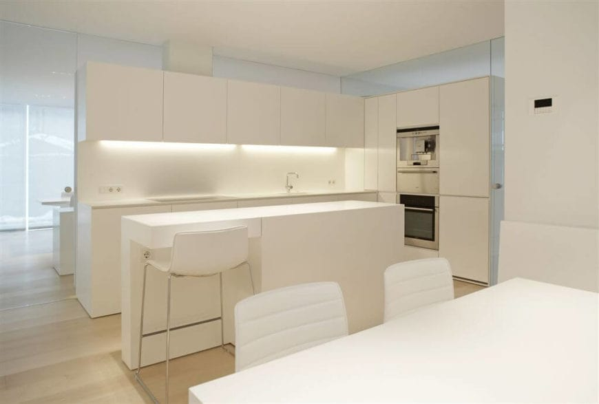This simple and elegant kitchen has no windows but makes up for it with mirrored walls behind the L-shaped structure that has modern creme cabinets and drawers matching those of the narrow kitchen island paired with a single modern white stool.