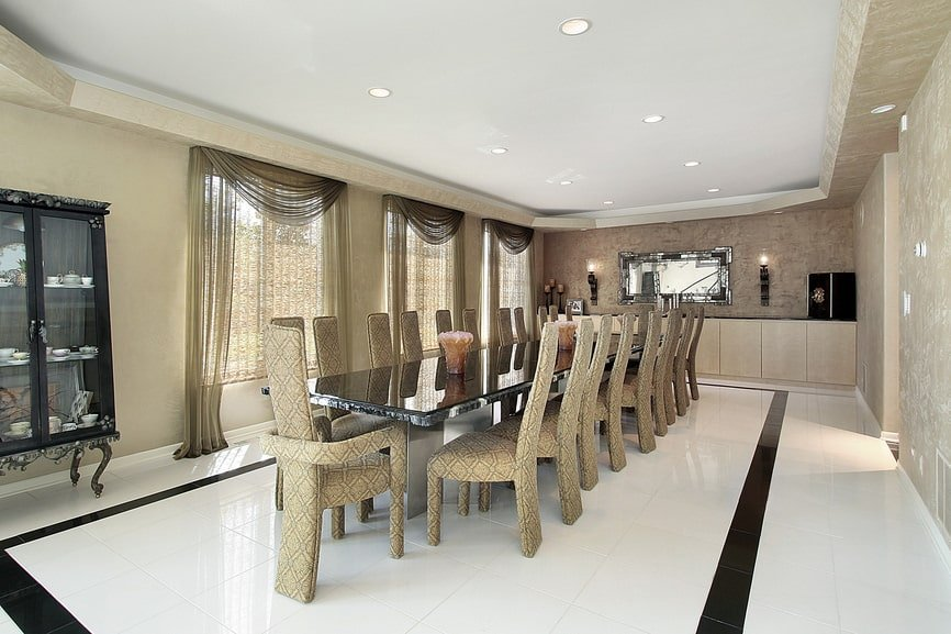 The spacious dining room boasts a long, slim dining table and stylish high back chairs over white tiled flooring contrasted by a black border. It has a tray ceiling and glazed windows covered in sheer curtains.