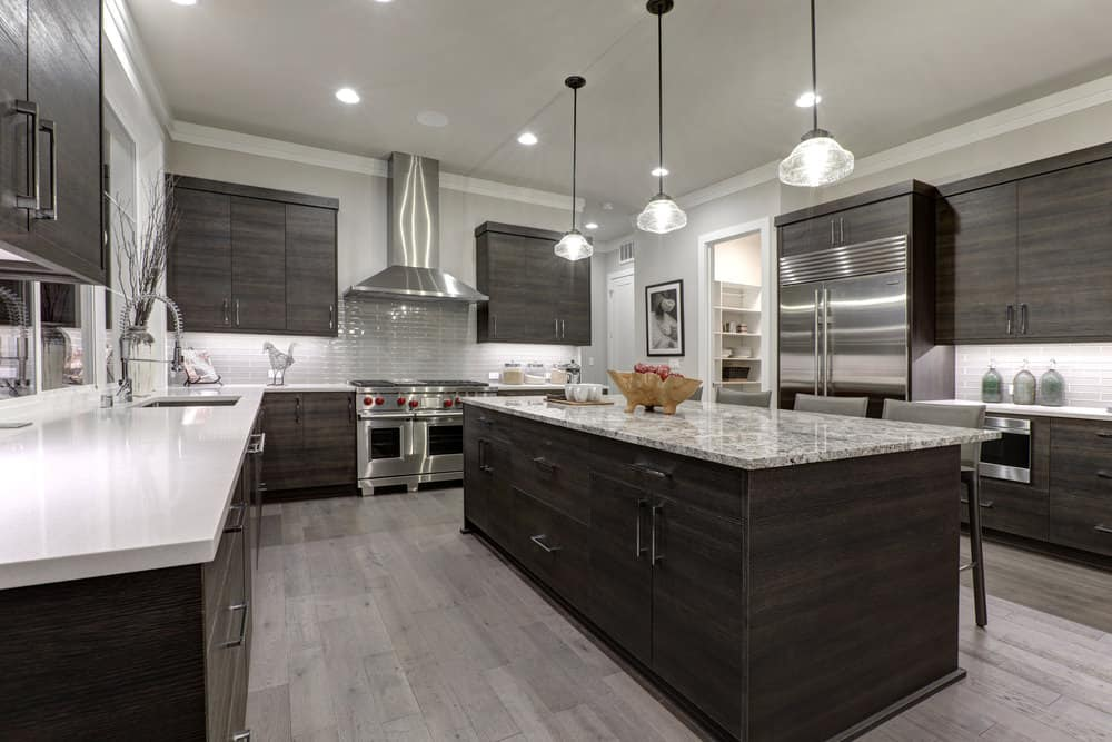 This is a large U-shaped kitchen with a large dark wooden kitchen island in the middle matching with the surrounding cabinetry that has a white countertop and light gray backsplash. This matches with the light gray walls and ceiling.