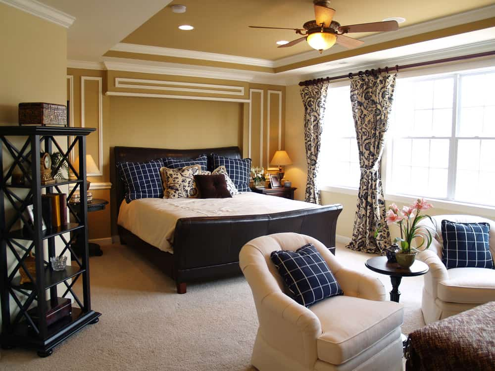 Large primary bedroom styled with wainscoting and patterned draperies covering the glazed windows. It is furnished with a black shelving unit and beige round back chairs in front of the leather bed flanked by dark wood nightstands.