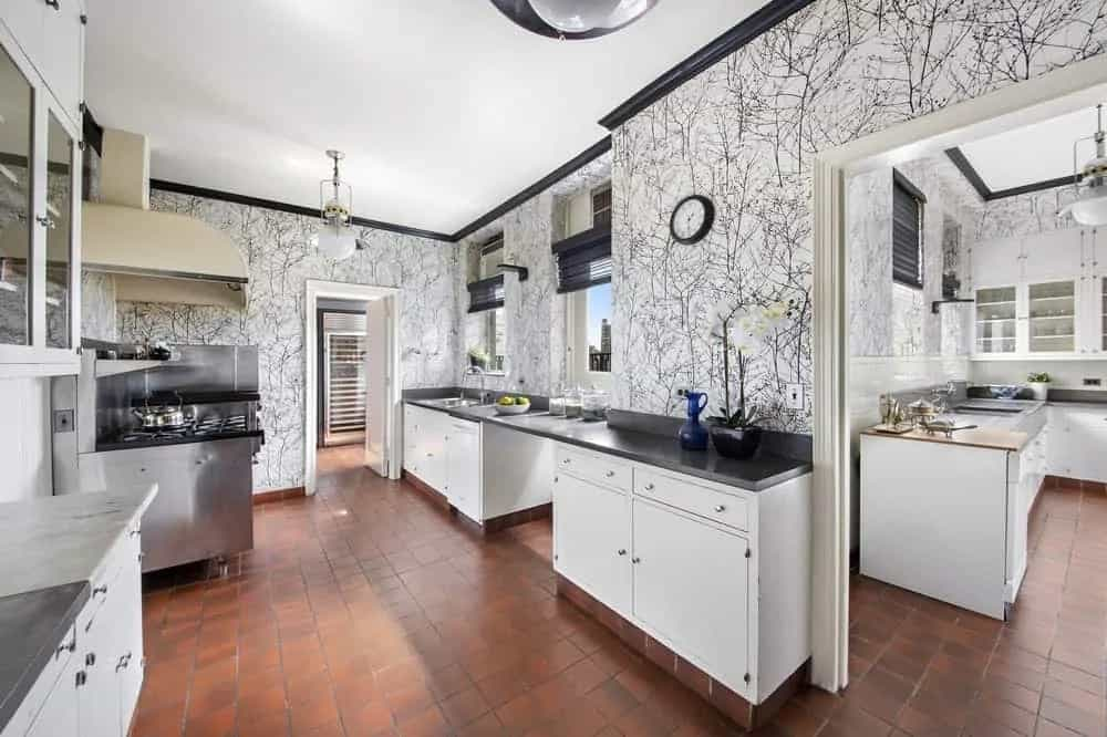 The spacious kitchen has a dark hardwood flooring that contrasts the light tone of the cabinetry topped with black countertops and detailed wallpaper.