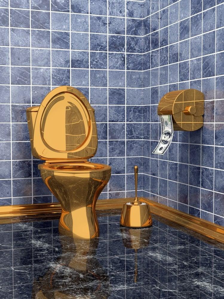 Golden toilet in a luxury blue bathroom.