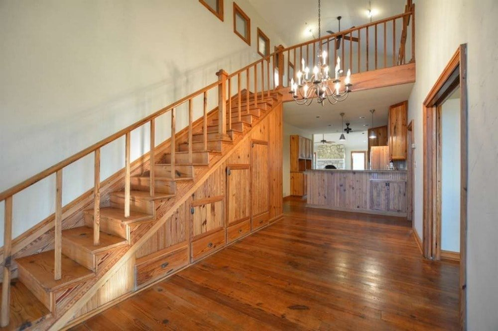 This is the charming foyer of the house with a hardwood flooring topped with a tall ceiling that hangs a chandelier over the area beside the straight wooden staircase.