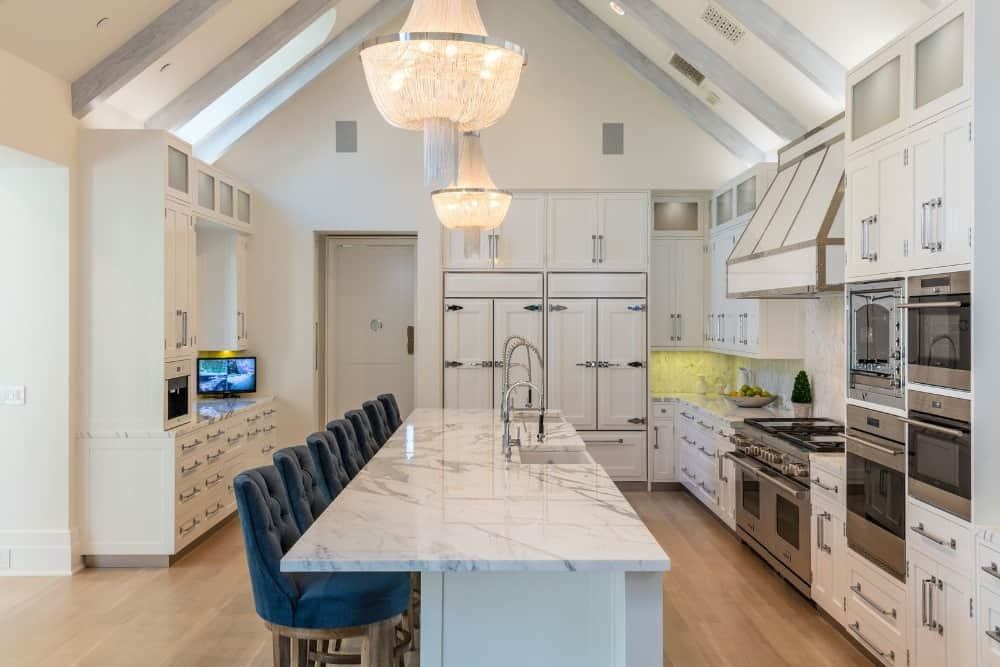 This kitchen offers a long center island featuring a gorgeous marble countertop and has a breakfast bar counter topped iwth a cathedral ceiling with exposed beams.