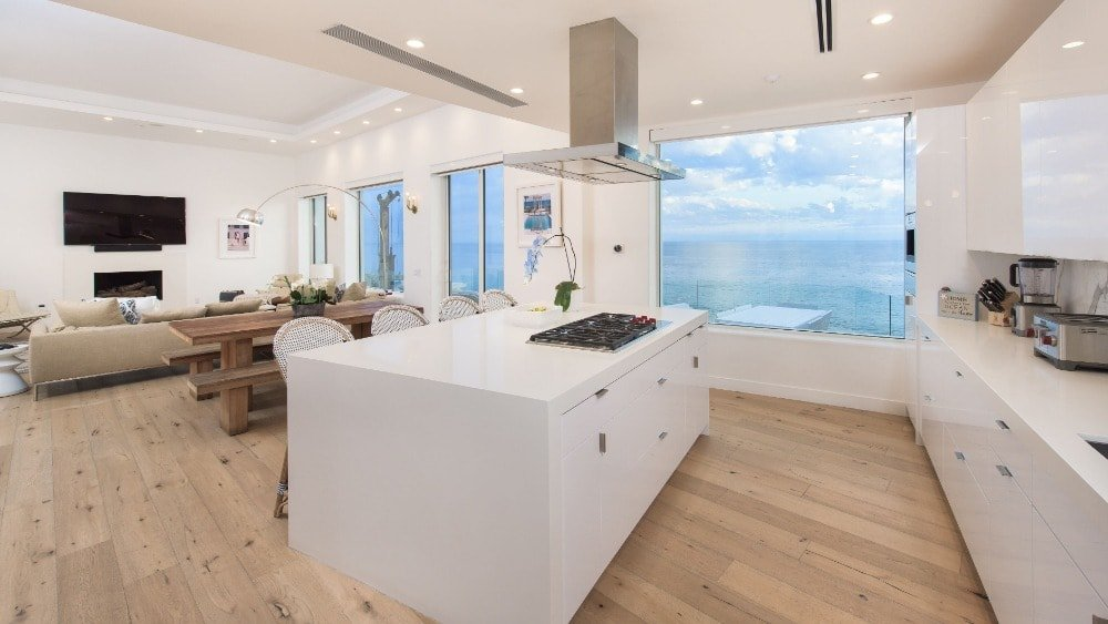 This charming kitchen has a large white kitchen island that houses the stove topped with a stainless steel vent. These are complemented by the light hardwood flooring and the large glass windows.