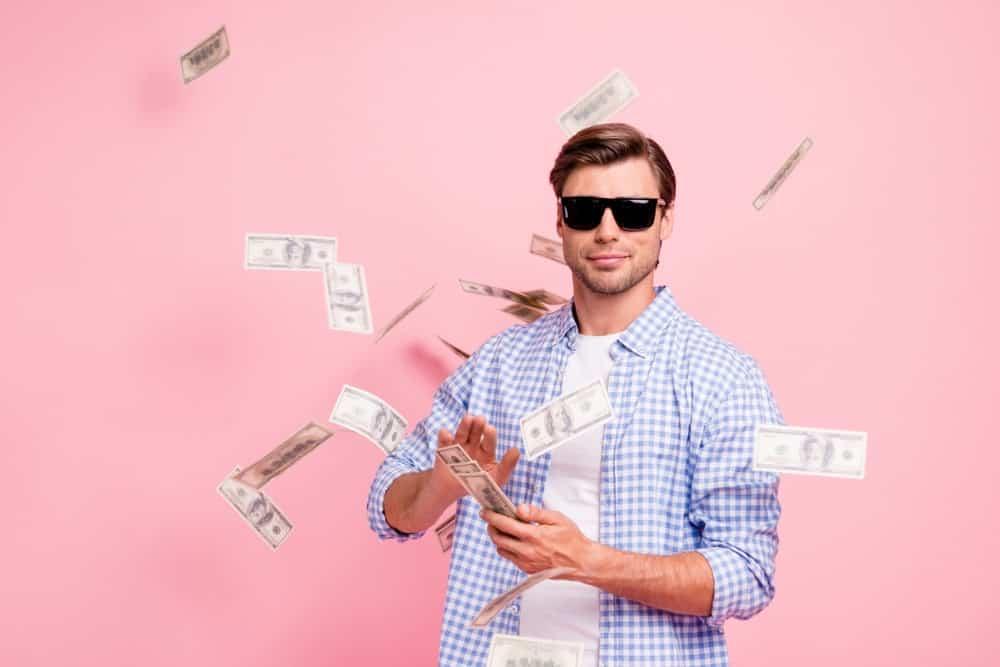 Man in dark shades spreading around cash from his hands.