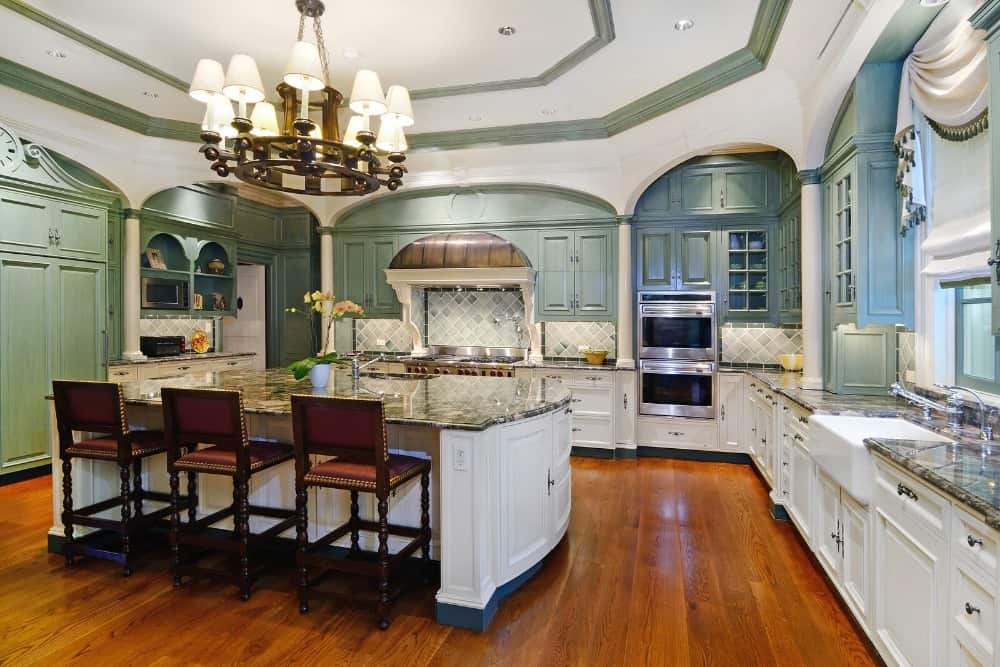 Kitchen with an L-shaped kitchen counter and a center island boasting a gorgeous kitchen countertop and a fancy chandelier ceiling light.