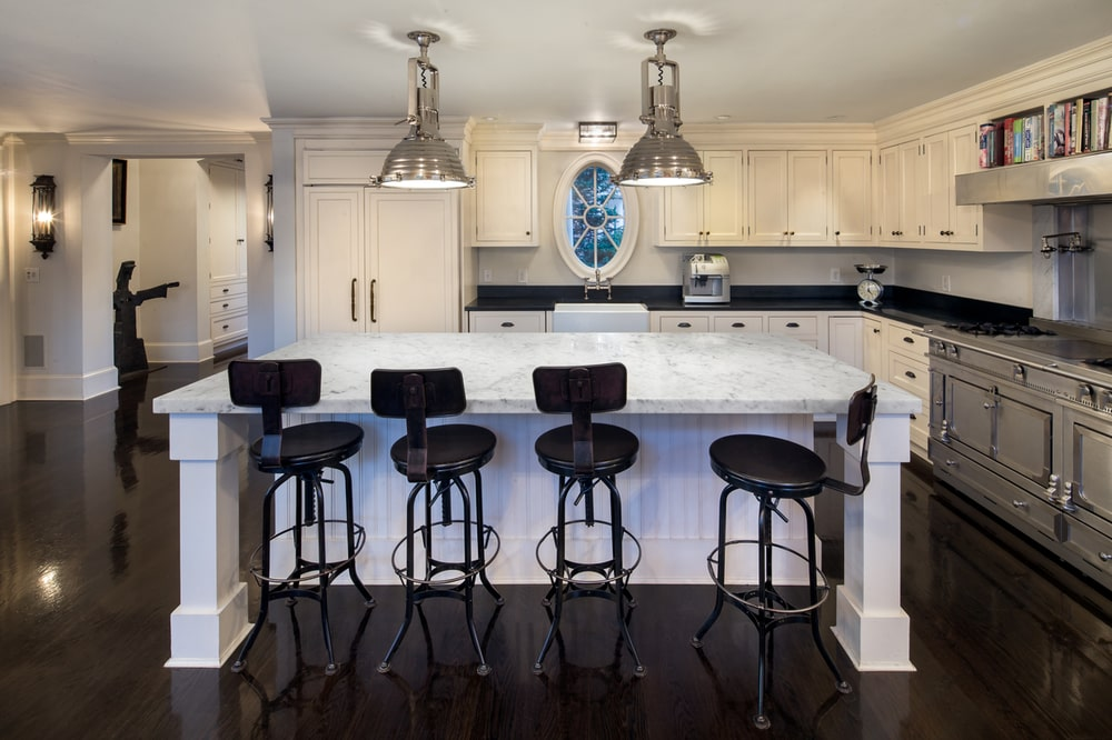 The kitchen has a bright white kitchen island, cabinetry and ceiling that hangs a couple of dome pendant lights over the white countertop.