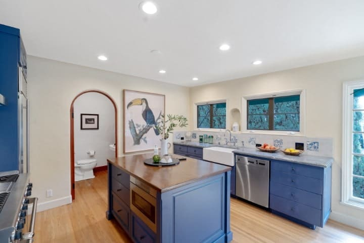 The kitchen has a small gray kitchen island that matches well with the cabinetry and the stainless steel appliances. These are then complemented by the hardwood flooring and the beige walls.