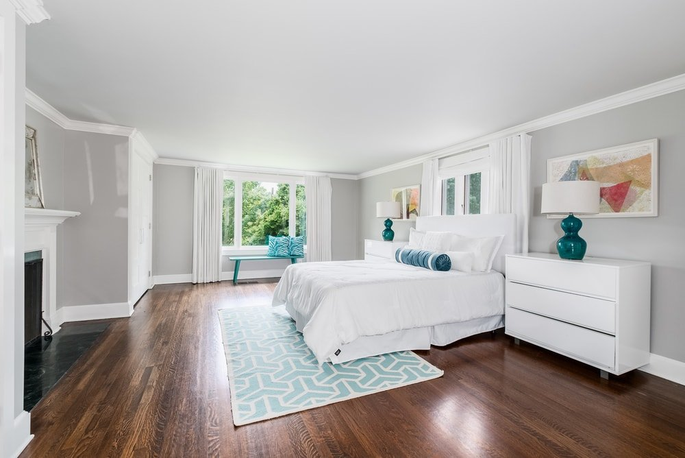 This is the primary bedroom with a large white bed adorned by the colorful patterned area rug underneath that tops the hardwood flooring.