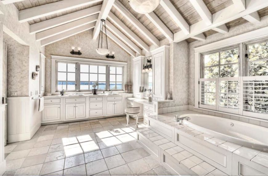 A spacious master bathroom with tiles flooring and a rustic vaulted ceiling with exposed beams. The room offers a drop-in tub, a sink counter with two sinks and a powder desk.
