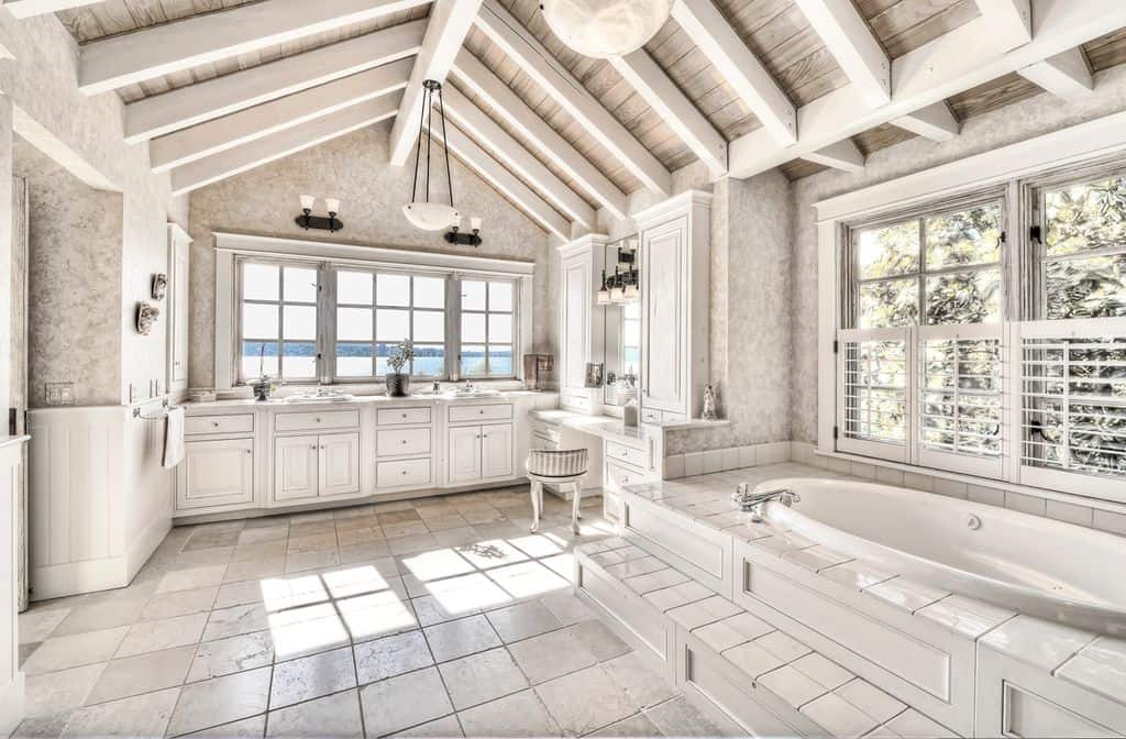 A spacious primary bathroom with tiles flooring and a rustic vaulted ceiling with exposed beams. The room offers a drop-in tub, a sink counter with two sinks and a powder desk.