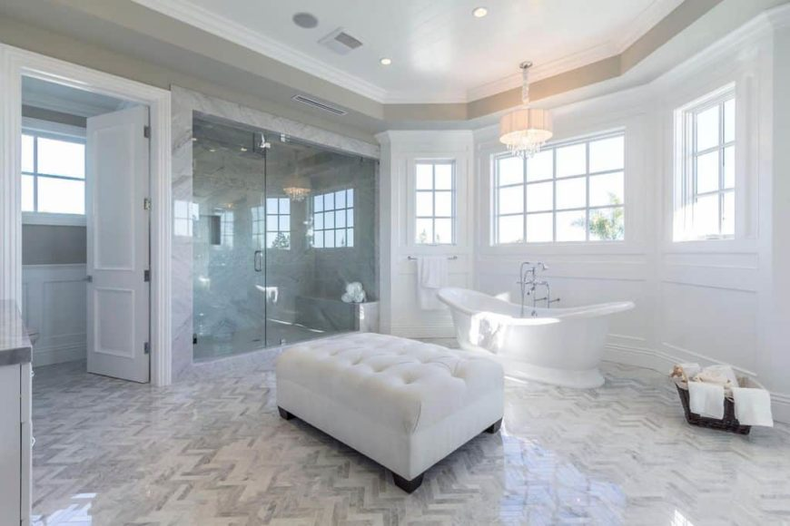 A master bathroom with stylish tiles flooring and a gorgeous tray ceiling. It offers a classy freestanding tub lighted by a charming chandelier together with a walk-in shower room.