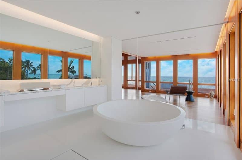 A bright master bathroom featuring white walls, white tiles floors and a white ceiling. It has a floating vanity sink counter and a round drop-in tub. The room also has glass windows overlooking the beautiful ocean view.