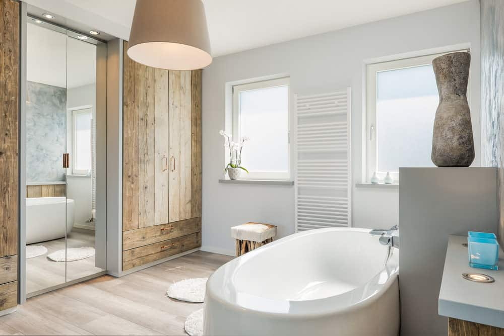 A primary bathroom offering a large modern freestanding tub and a walk-in shower room, along with a rustic reach-in closet.