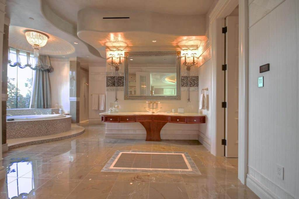 Spacious primary bathroom boasting a stunning sink counter and a drop-in tub by the window. The room offers elegant ceiling lights, shiny tiles flooring and a stunning ceiling.