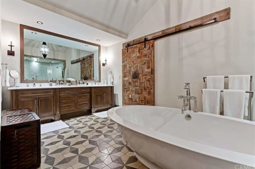 Large master bathroom with beautifully decorated tiles flooring. It has a sink counter with two sinks along with a large freestanding tub.