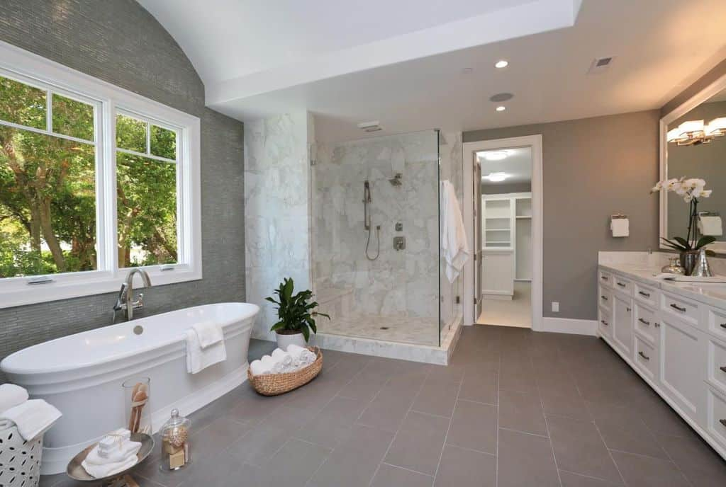 This primary bathroom features gray tiles floors, gray walls and a white custom ceiling. It offers a freestanding tub by the windows along with a walk-in shower room set in the corner.