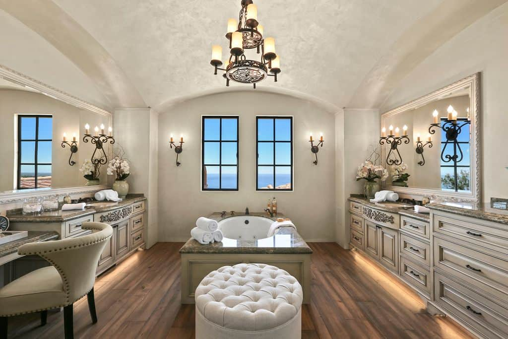 A primary bathroom offering a pair of elegant sinks, with the drop-in soaking tub set in between. There's a classy ottoman seat and a powder desk as well. The area is lighted by a charming chandelier hanging from the stunning ceiling.