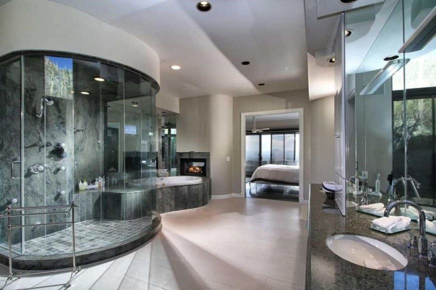 Modern master bathroom boasting a stylish walk-in shower room along with a drop-in soaking tub on the side featuring a fireplace. The sink counter features a granite countertop as well.