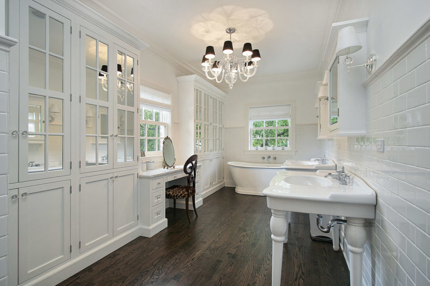 Spacious master bathroom with hardwood floors and white walls. it has a powder desk, two sink counters and a freestanding soaking tub. The room is lighted by a fancy chandelier.