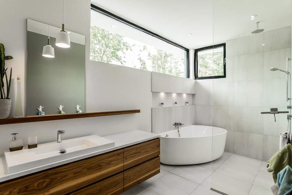 Modern primary bathroom with a wide floating vanity sink and a corner freestanding bathtub near the shower area.