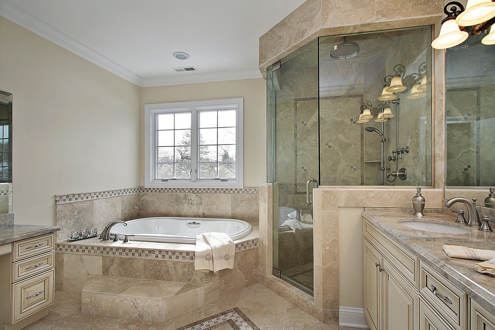 Primary bathroom with beige tiles floors. It offers a drop-in soaking tub on a tiles platform, along with a corner walk-in shower and a sink counter lighted by wall lights.