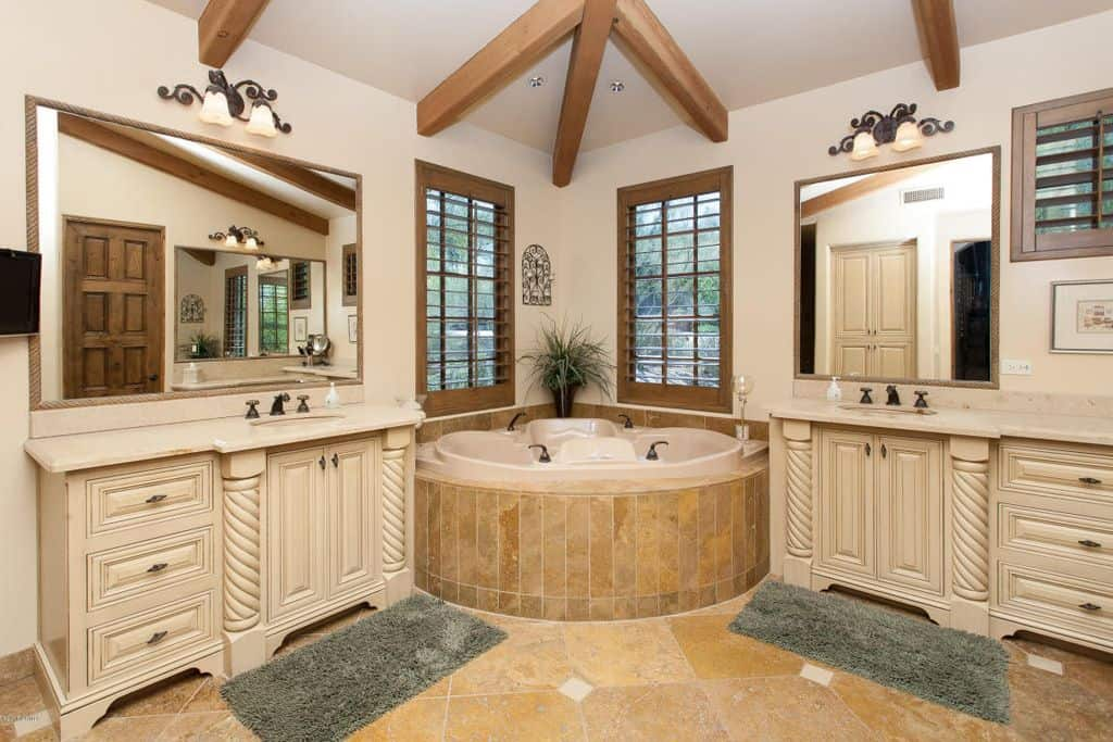 This primary bathroom offers a corner tub and two sink counters lighted by wall lights. The room also features beige tiles flooring and a ceiling with beams.