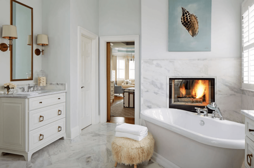 This master bathroom boasts gorgeous marble tiles flooring. It has a single sink counter lighted by a pair of wall lights. There's a large freestanding tub as well with a fireplace nearby.