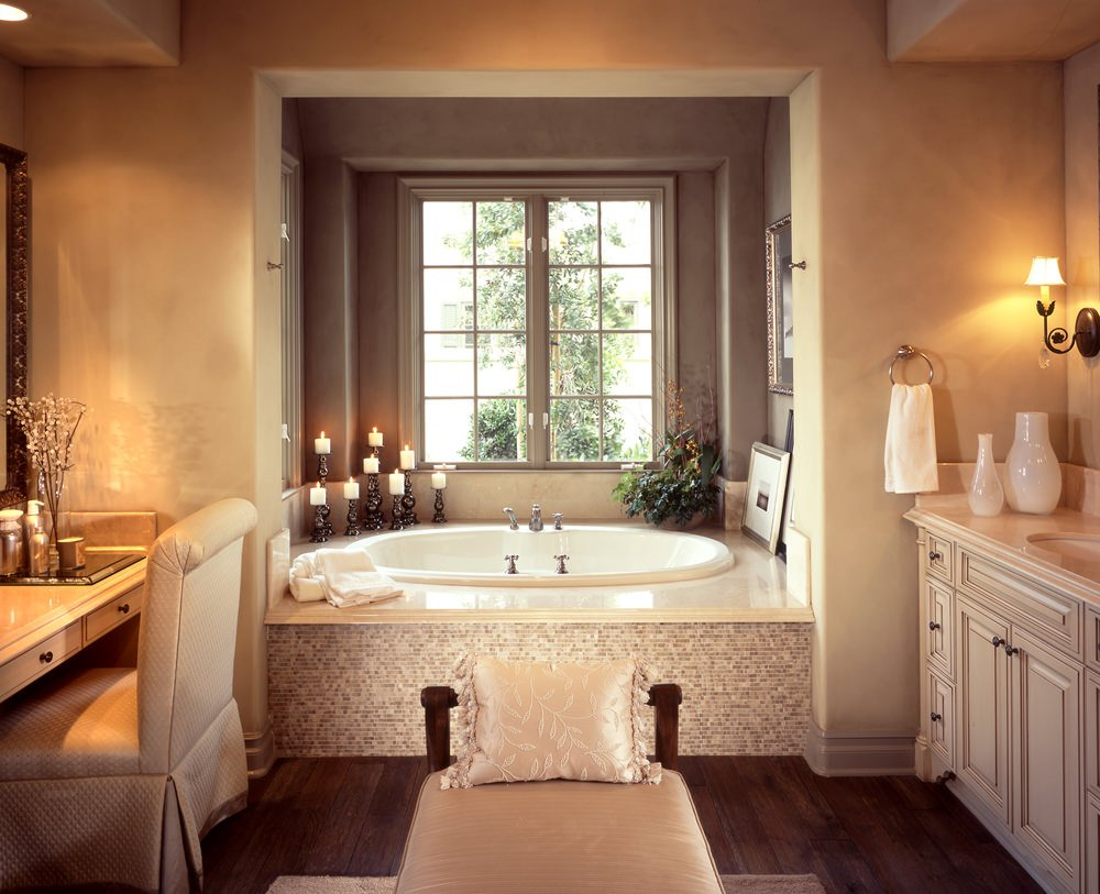 A primary bathroom with hardwood flooring topped by an area rug. It has a powder desk area, a sink counter lighted by wall lights and a drop-in soaking tub with candle lights lighting.