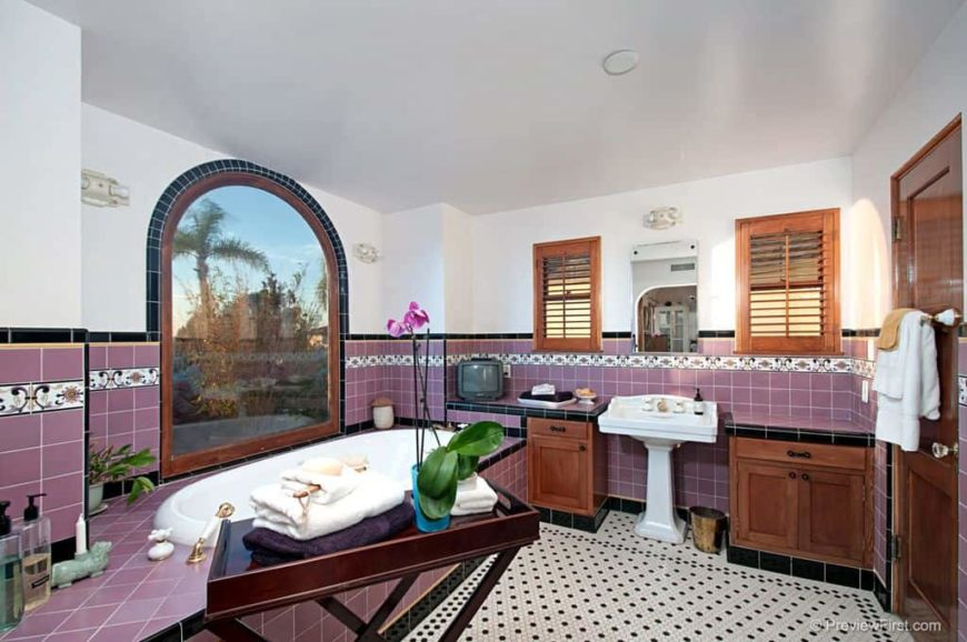 Master bathroom with stylish tiles flooring, purple tiles walls and a purple tiles bathtub platform. This bathroom also has a pedestal sink.