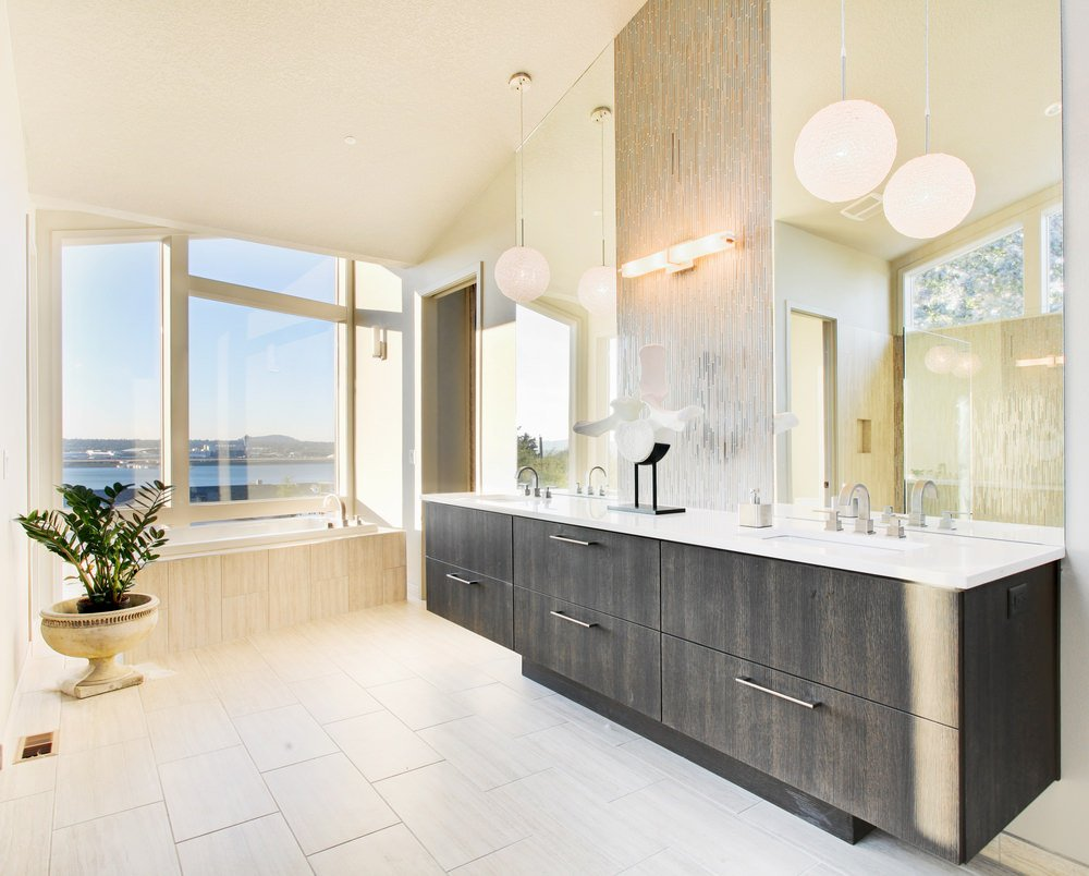 Primary bathroom featuring a tall ceiling and tiles flooring, together with glass windows overlooking the peaceful surroundings. It offers a walk-in shower room and a stylish sink counter with two sinks, lighted by pendant lights.