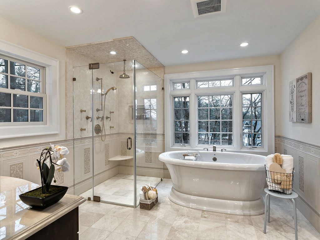 Primary bathroom featuring tiles flooring and a classy freestanding soaking tub, together with a sink counter with a marble countertop and a walk-in glass shower room.
