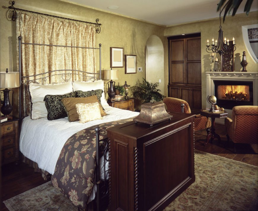 This primary bedroom offers an ornate metal bed in between wooden nightstands along with a sitting area by the fireplace illuminated by a wrought iron chandelier. It has an open archway and wide plank flooring topped by a classic area rug.